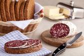 Served kitchen table, sandwich on napkin, salami, breadbasket, s — Stock Photo
