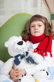Little sick girl with scarf embraces toy bear in bed close-up — Stock Photo