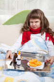 Little sick girl with scarf in bed is taking medicine — Stock Photo