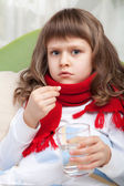 Little sick girl with scarf in bed is taking a pill — Stock Photo