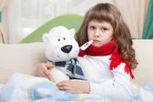 Little sick girl with thermometer embraces toy bear in bed — Stok fotoğraf