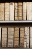 Covers of old ancient books monuscripts on shelves in bookcase — Stock Photo