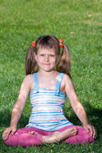 Smiling child sit and meditate in asana on green grass — Stock Photo