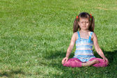 Little child sit and meditate in asana on green grass — Stock Photo