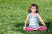 Little girl sits in the shade in asana on grass — Stock Photo