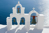 Calm sea, white church arch, cross, bells Island Santorini Greec — Stock Photo