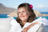 Little girl in white bathrobe relaxing on terrace sea background — Stock Photo