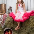 Portrait of funny girl near pail with  apples in hayloft — Stock Photo