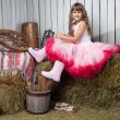 Portrait of funny girl near pail with  apples in hayloft - Stock Photo