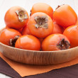 Exotic tropic orange fruits  persimmon served in wooden plate - Stock Photo