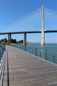 Parque das Nações footpath and famous Vasco da Gama bridge. Lisbon, Portugal. — Stock Photo