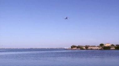 Hava yolculuğu - faro Havaalanı, ria formosa, doğal koruma bölgesi içinde yer alan ticari uçak iniş görünümünü siluet. Algarve, Portekiz — Stok video