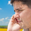 Royalty-Free Stock Photo: Handsome man in sunflower field making phone call