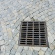 Sewer cover at paved stone — Stock Photo