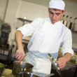 Young male chef cooking meal — Stock Photo