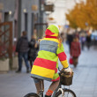 Stock Photo: Young woman cycling on European street