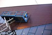 Construtor em um scissor lift plataforma em um local de construção — Foto Stock