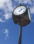 Old street clock over blue sky background — Zdjęcie stockowe