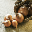 Onions scattered from wicker basket - Stock Photo
