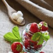 Stock Photo: Red strawberries in glass jar on sackcloth