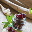 Red cherries in glass jar on sackcloth - Stock Photo