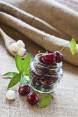 Red cherries in glass jar on sackcloth — Stock Photo