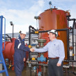 Two petrochemical contractors closing a deal in front of an oil - Stockfoto