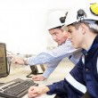 Senior and junior engineers discussing work together in office - Foto Stock
