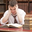 Stressed young student with a pile of books to read — Stockfoto