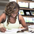 Pretty black african student girl reading books in library — Foto de Stock