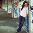 Stock Photo: Young pretty girl posing in abandoned graffiti painted building
