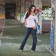 Young pretty girl posing in abandoned graffiti painted building — Stock Photo