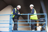 Foreman and construction worker at constraction site — Stock Photo