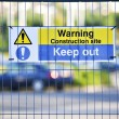 Warning construction area sign on site fence - Stock Photo