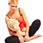 Beautiful young blonde girl with plush bear — Stock Photo