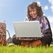 Beautiful young student using laptop on grass — Stock Photo #24564209
