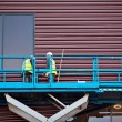 Builder on a Scissor Lift Platform at a construction site — Stock Photo