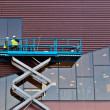 Stock Photo: Builder on a Scissor Lift Platform at a construction site