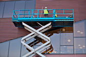 Builder on a Scissor Lift Platform at a construction site — Stock Photo
