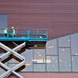 Builder on a Scissor Lift Platform at a construction site — Stock Photo #29051397