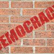 Stock Photo: Old brick wall texture with DEMOCRACY inscription
