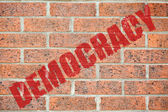 Old brick wall texture with DEMOCRACY inscription — Stock Photo