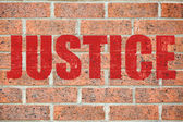 Old brick wall texture with JUSTICE inscription — Stock Photo