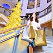 Stock Photo: Beautiful young woman holding shopping bags