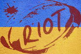 Ukraine flag painted on old concrete wall with RIOT inscription — Stock Photo