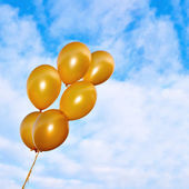 Golden flying balloons on the sky background — Stock Photo