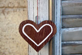 Artifact in the form of heart on the background of wooden shutte — Stock Photo