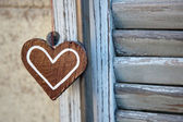 Artifact in the form of heart, on the wooden shutters background — Stock Photo