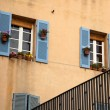 Window with blue shutters on beige walls in Marseille — Stok fotoğraf