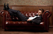 A man in a suit lying on the couch — Stock Photo